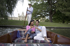 A couple enjoying an early evening river ride on the Cam whilst drinking champagne.