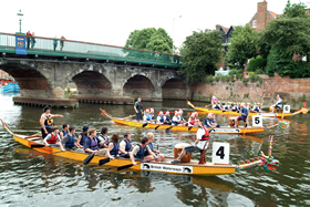 Dragon boats row under a bridge during the Dragon Boat Festival