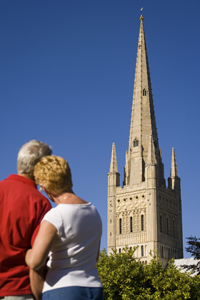 Couple looking towards the fine 15th Century spire of Norwich Cathedral