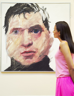 Woman looking at portrait by Sam Walsh in the Walker Art Gallery